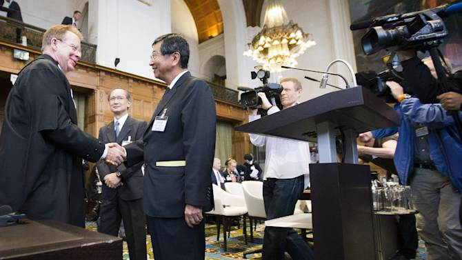 CORRECTS ID OF PERSON AT LEFT General Counsel Bill Campbell, left, shakes hands with Japanese Deputy Minister of Foreign Affairs Koji Tsuruoka, second left, at the International Court of Justice in The Hague, Netherlands, Wednesday, June 26, 2013. Australia is urging the United Nations' highest court to ban Japan's annual whale hunt. Lawyers for Australia will argue at the International Court of Justice on Wednesday that Japan harpoons minke whales each year in the icy waters around Antarctica in breach of a 1986 moratorium on commercial whaling. Japan will respond next week by telling judges that the hunt is for scientific research and is allowed under the 1946 International Convention for the Regulation of Whaling. The court will take months to issue a final and binding decision.(AP Photo/Jiri Buller)