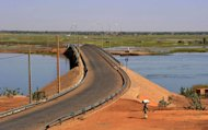 A woman walks by the Gao bridge on the Niger River guarded by French soldiers on February 3, 2013 in Gao
