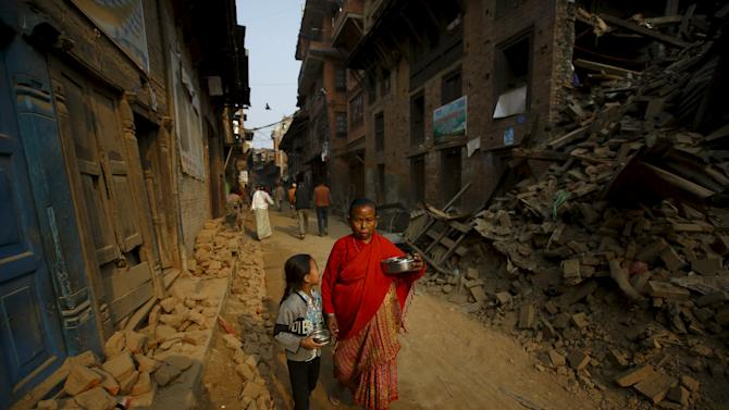 A woman and a child returning from a temple, walk past damaged and collapsed houses following April 25 earthquake at Bhaktapur