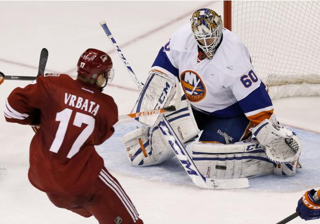 New York Islanders' Kevin Poulin (60) makes a save on a shot by Phoenix Coyotes' Radim Vrbata (17), of the Czech Republic, during the third period of an NHL hockey game Thursday, Dec. 12, 2013