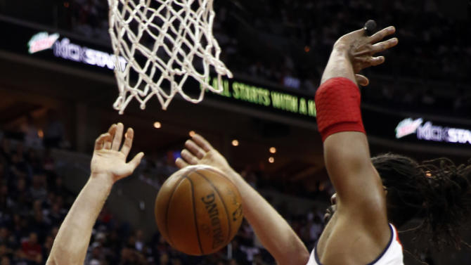 Toronto Raptors forward Tyler Hansbrough (50) loses control of the ball as he attempts to shoot over Washington Wizards forward Nene (42), from Brazil, in the first half of Game 3 in the first round of the NBA basketball playoffs Friday, April 24, 2015, in Washington. (AP Photo/Alex Brandon)