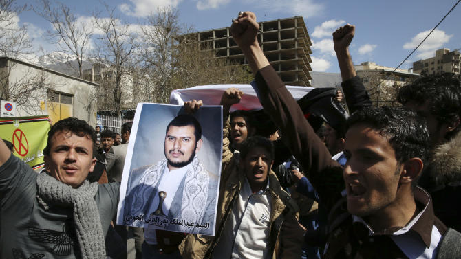 Scores of Yemeni expatriates, including students and clerics, chant slogans while holding a poster of the Yemeni Shiite Houthi rebel leader Abdul-Malik al-Houthi, during a protest against Saudi-led airstrikes on their homeland, in front of the Saudi Embassy, in Tehran, Iran, Wednesday, April 1, 2015. (AP Photo/Vahid Salemi)