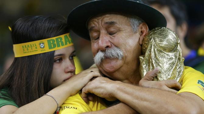 Brazilian fans react to their team's loss at the end of their 2014 World Cup semi-finals against Germany at the Mineirao stadium in Belo Horizonte