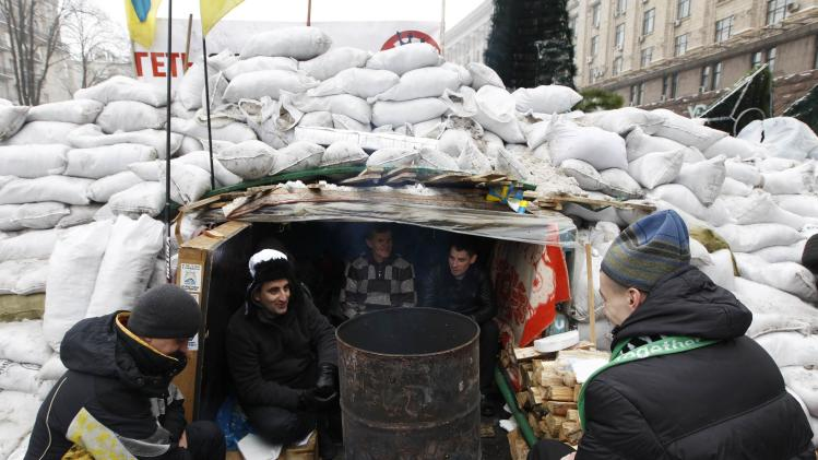 People spend time at a barricade set up by pro-European integration protesters in central Kiev