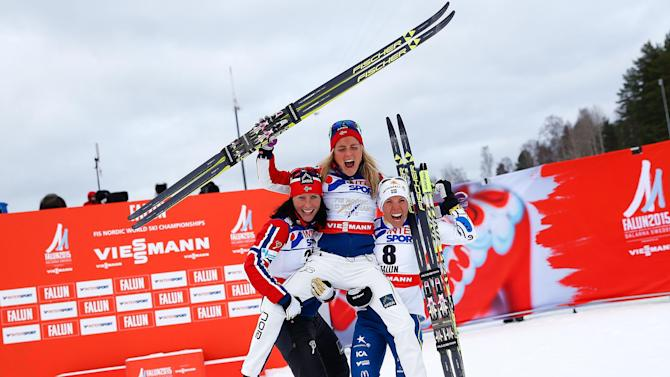 Norway's Johaug, Bjoergen and Sweden's Kalla celebrate after the women's cross country 30 km mass start classic race at the Nordic World Ski Championships in Falun