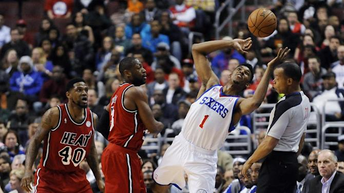 Philadelphia 76ers' Nick Young (1) reaches up to keep the ball in play in front of Miami Heat's Dwyane Wade (3) and Udonis Haslem (40) during the first half of an NBA basketball game, Saturday, Feb. 23, 2013, in Philadelphia. (AP Photo/Michael Perez)