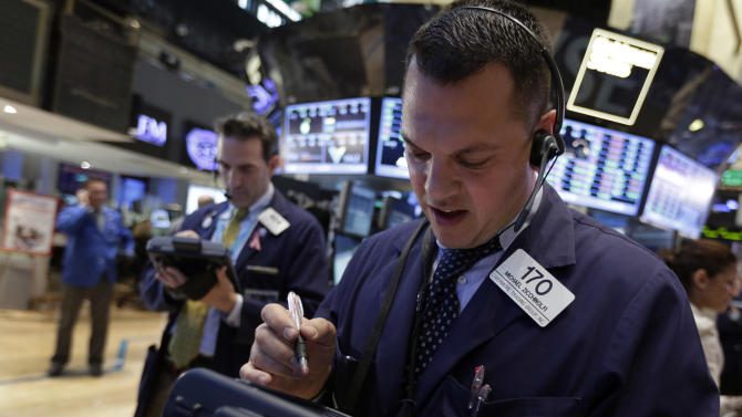 Trader Michael Zicchinolfi, right, works on the floor of the New York Stock Exchange Tuesday, May 7, 2013. The Dow Jones industrial average punched through another milestone Tuesday: its first close above 15,000. (AP Photo/Richard Drew)