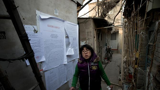 In this photo taken on Dec. 26, 2012, a Chinese woman walks out from her Hutong home with a demolition notice seen on the wall near the historical Drum and Bell Tower in Beijing. The district government wants to demolish these dwellings, move their occupants to bigger apartments farther from the city center and redevelop a square in 18th century Qing Dynasty fashion. (AP Photo/Andy Wong)