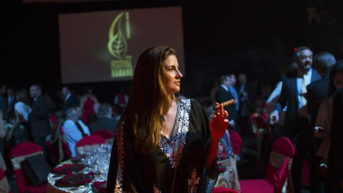 Woman smokes a cigar during the gala dinner of the closing of the XVII Habanos Festival in Havana