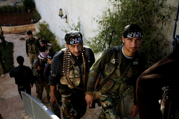 In this Wednesday, Nov. 14, 2012 photo, Syrian fighters of The Beloved of Allah, brigade hold their weapons before fighting with government forces on the outskirts of Aleppo. The Beloved of Allah began with ten men, five rifles, one rickety machine gun and a few rocket-propelled grenades soon discovered to be duds. It was born in Maaret Misreen, a town where tractors nearly outnumber cars between the provincial capital of Idlib and the Turkish border to the north. Their leader, 35-year-old Mustafa Filfileh, had no military experience and little idea how to face one of the Mideast&#39;s strongest armies. He didn&#39;t even know how to drive. They learned fast. In November, the brigade called The Beloved of Allah braced for its biggest challenge yet, one that would make clear how far its members had come and how far the war had brought them from their former lives. (AP Photo/Khalil Hamra)