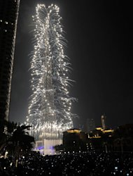 Revellers watch fireworks illuminating the Burj Khalifa in Dubai on January 1, 2013