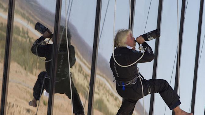 FILE- This Oct. 17, 2011 file photo shows British billionaire Sir Richard Branson drinking champagne after repelling down the side of the new Spaceport America hangar in Upham, N.M. As the nation's first launch station to send people to space nears completion, some see signs New Mexico may have reached for the stars _ and got stuck in the bad economy. (AP Photo/Matt York, File)