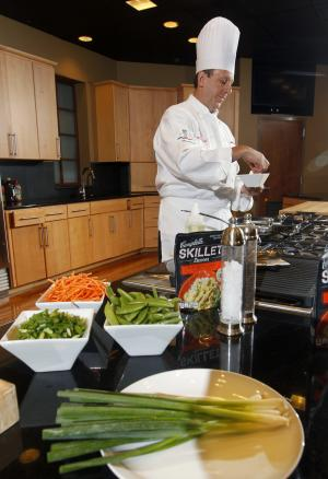 In this Friday, Aug. 24, 2012 photo, Campbell Soup Company chef Thomas W. Griffiths prepares fresh produce to add to Campbell's new Green Thai Curry Skillet sauce at the company's headquarters in Camden, N.J. Last year, the company began a quest that led executives to trendsetting cities including Portland, Ore. and London to figure out how to make soups that appeal to younger, finicky customers. In the year ahead, the 143-year-old company plans to roll out 50 new products such as Moroccan Style Chicken and Spicy Chorizo. The ingredients may also surprise those used to a plain bowl of chicken with stars: tomatillos, coconut milk and shitake mushrooms. (AP Photo/Mel Evans)