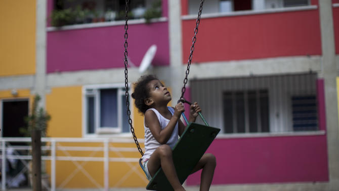 In this photo taken April 11, 2012, a child plays on a swing in Rocinha slum in Rio de Janeiro, Brazil. Setbacks in a security program meant to take back territory from the drug trade have shown the immense challenge of pacifying the city's violent slums and raised questions about the state's ability to keep the peace as Rio prepares to take the world stage not just for the Olympics but the 2014 World Cup, which will host its headline events in Rio.  (AP Photo/Felipe Dana)