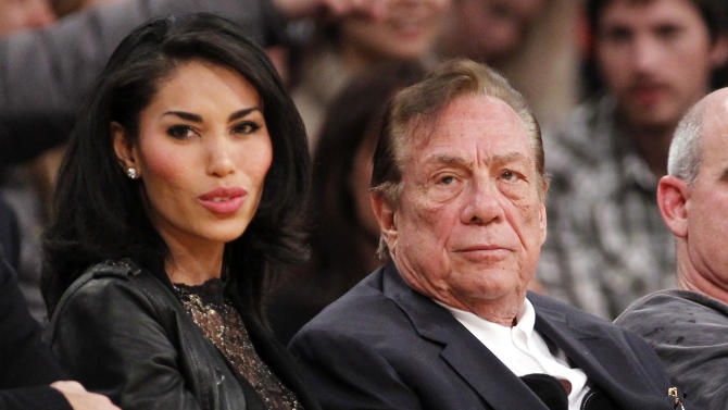 FILE - In this Dec. 19, 2010, file photo, Los Angeles Clippers owner Donald Sterling, third right, sits with V. Stiviano, left, as they watch the Clippers play the Los Angeles Lakers during an NBA preseason basketball game in Los Angeles. NBA commissioner Adam Silver announced Tuesday, April 29, 2014, that he is banning the owner for life from the Clippers organization over racist comments in recording. (AP Photo/Danny Moloshok, File)