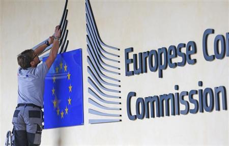 A worker adjusts and cleans the logo of the European Commission at the entrance of the EC headquarters in Brussels