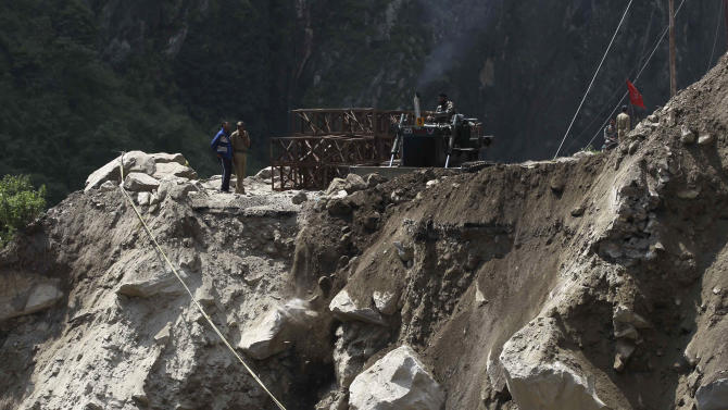 Workers stand next to a road damaged by floods and landslides in Govindghat, India, Saturday, June 22, 2013. Soldiers were working to evacuate tens of thousands of people still stranded Saturday in northern India where nearly 600 people have been killed in monsoon flooding and landslides. (AP Photo/Rafiq Maqbool)