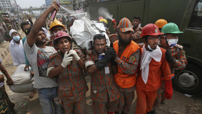 The body of a Bangladeshi garment worker is carried by rescue workers after being removed from the rubble of a building that collapsed Wednesday in Savar, near Dhaka, Bangladesh, Saturday, April 27, 2013. Police in Bangladesh arrested two owners of a garment factory in a shoddily-constructed building that collapsed this week, killing at least 324 people, as protests spread to a second city Saturday with hundreds of people throwing stones and setting fire to vehicles. (AP Photo/Kevin Frayer)