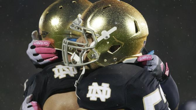 Notre Dame linebacker Manti Te'o, left, celebrates with defensive end Justin Utupo (53) after Notre Dame defeated Stanford 20-13 in overtime in an NCAA college football game in South Bend, Ind., Saturday, Oct. 13, 2012. (AP Photo/Nam Y. Huh)