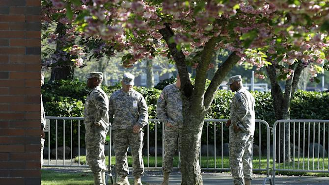 Soldiers assisting with communications and security tasks stand outside the building at Joint Base Lewis-McChord, Wash., where the court-martial for U.S. Army Sgt. John Russell began, Monday, May 6, 2013. Russell has already pleaded guilty to killing five fellow servicemen in Iraq in 2009, and and prosecutors are expected to argue that the killings were premeditated. (AP Photo/Ted S. Warren)