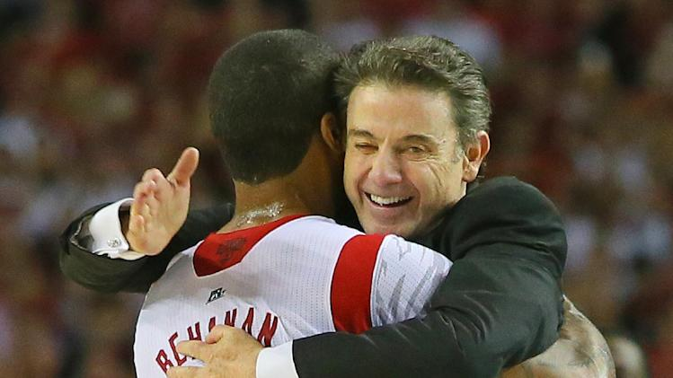 Louisville forward Chane Behanan embraces head coach Rick Pitino who gives him a pat on the back after defeating Michigan to win the NCAA Division I National Championship on Monday, April 8, 2013, in Atlanta. Louisville beat Michigan 82-76 for NCAA title. (AP Photo/Atlanta Journal Constitution, Curtis Compton)