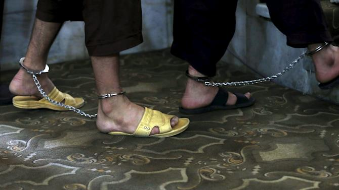 Two of four Afghan men arrive at court while chained at their feet for their trial in connection with the killing of a 27-year-old woman, in Kabul