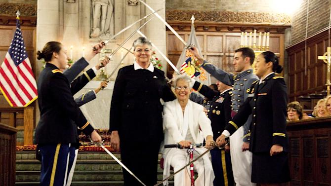 In this photo provided by Outserve-SLDN, Brenda Sue Fulton, center left, and Penelope Gnesin, proceed through an honor guard forming an arch of raised swords after exchanging wedding vows at the U.S. Military Academy at West Point, N.Y.  Saturday, Dec. 1, 2012. Their ceremony marks the first time a same sex couple had their wedding in the Cadet Chapel, the landmark gothic church that is a center for spiritual life at the Academy. The chaplain and woman at left are unidentified. (AP Photo/Outserve-SLDN, Jeff Sheng)