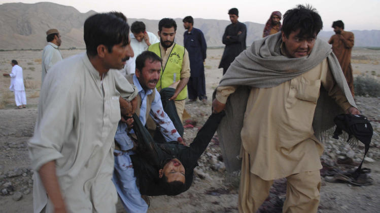 People carry the body of a shooting victim to an ambulance in Mastung near Quetta, Pakistan on Tuesday, Sept 20, 2011. Gunmen opened fire on minority Shiite Muslim pilgrims traveling through southwest Pakistan on Tuesday, killing 26 people in an apparent sectarian attack, officials and survivors said. (AP Photo/Arshad Butt)