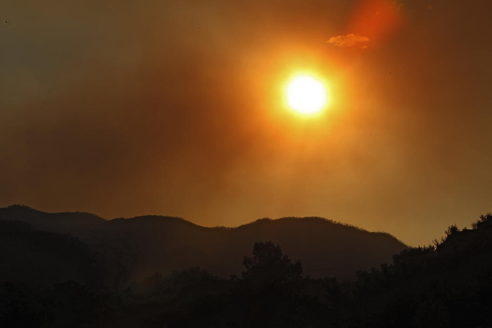 The sun sets amidst smoke from the High Park Fire near Bellvue,  Colo., on Monday,  June 18, 2012. The wildfire has now burned about 90 square miles and destroyed more than 180 homes. (AP Photo/Ed Andrieski)