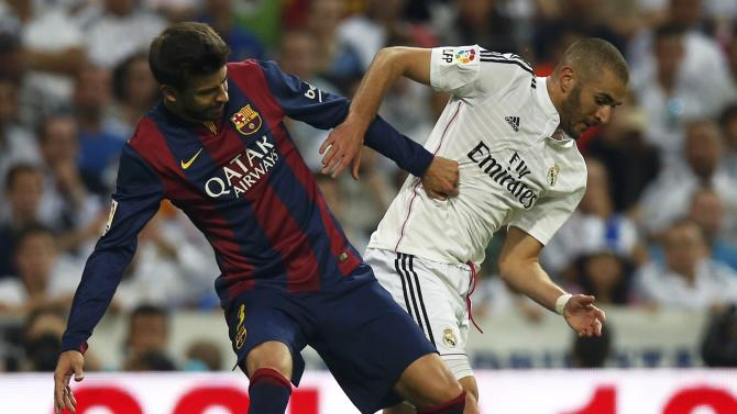 "Real Madrid?s Benzema is challenged by Barcelona?s Pique during their Spanish first division ""Clasico"" soccer match at the Santiago Bernabeu stadium in Madrid"