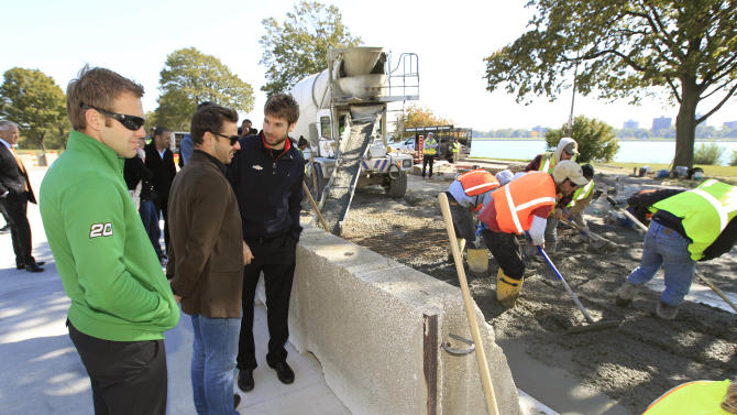 From left, IndyCar drivers Ed Carpenter, Oriol Servia, of Spain, and Will Power, of Australia, stand nearby as work crews continue the repaving of the Belle Isle auto-racing track in Detroit, Tuesday, Oct. 9, 2012. The drivers toured the track that fell apart last year when open-wheel racing made its return to the Motor City. (AP Photo/Carlos Osorio)