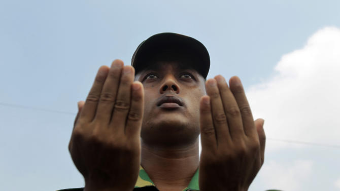A Bangladesh army soldier offers prayers for the souls of the 1,127 people who died in the garment building structure collapse last month, in Savar, Bangladesh, Tuesday, May 14, 2013. The Islamic prayer service was held a day after the army ended the nearly three-week, painstaking search for bodies among the rubble of the worst tragedy in the history of the global garment industry and turned control of the site over to the civilian government for cleanup. (AP Photo/A.M. Ahad)