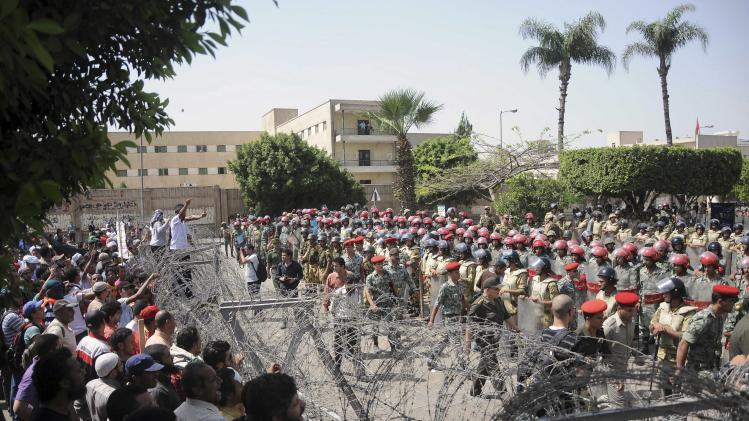 Protesters and security forces are separated by barbed wire in Cairo, Egypt. Nearly a dozen people were killed in clashes that broke out Wednesday when apparent supporters of the ruling military council attacked a mostly Islamist crowd staging a sit-in outside the Ministry of Defense in Cairo to call for an end to the generals' rule/ (AP Photo/Mohammed Asad)