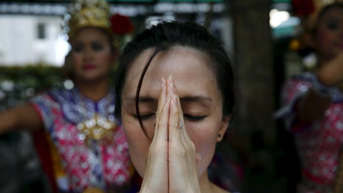 A woman prays at Erawan Shrine, the site of the recent bomb blast, in Bangkok