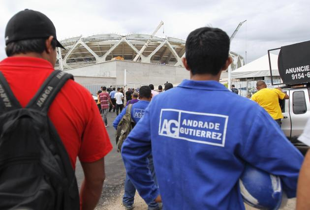 Workers from the Andrade Gutierrez construction company gather outside the Arena Amazonia stadium in Manaus