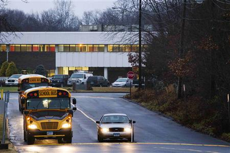 School buses drive past a police vehicle outside of the entrance for Chalk Hill Middle School, where students displaced from Sandy Hook Elementary School will begin their classes on Tuesday in Monroe, Connecticut, December 17, 2012. REUTERS/Lucas Jackson