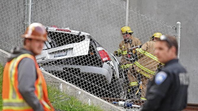 Emergency personnel work Friday, April 17, 2015, near a vehicle that drove over the side of a bridge and landed 100 feet below on railroad tracks in Tacoma, Wash., killing the driver. (David Montesino/The News Tribune via AP)