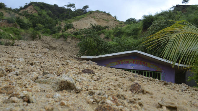 A small chapel is engulfed in rock and mud from a landslide triggered by heavy rains brought on by Tropical Storm Manuel on the outskirts of Acapulco, Mexico, Monday, Sept. 16, 2013. Tropical Storm Ingrid and remnants of Tropical Storm Manuel drenched Mexico's Gulf and Pacific coasts, flooding towns and cities in a national emergency that federal authorities say has caused at least 34 deaths. (AP Photo/Bernandino Hernandez)