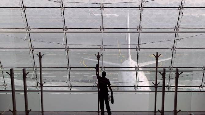 In this Sunday, Feb. 10, 2013, photo a laborer cleans a window at the new Concourse A of the Dubai airport in Dubai, United Arab Emirates. For generations, international fliers have stopped over in London, Paris and Amsterdam. Now, they increasingly switch planes in Dubai, Doha and Abu Dhabi, making this region the new crossroads of global travel. The switch is driven by both the airports and airlines, all backed by governments that see aviation as the way to make their countries bigger players in the global economy. (AP Photo/Kamran Jebreili)
