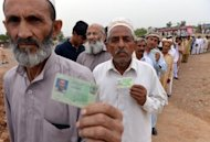 Pakistani voters display their national identity cards as they queue up to cast their vote outside a polling station in Islamabad on May 11, 2013. Pakistani voters went to the polls Saturday, braving Taliban threats to cast their ballots in an election marking a historic democratic transition for the nuclear-armed state.