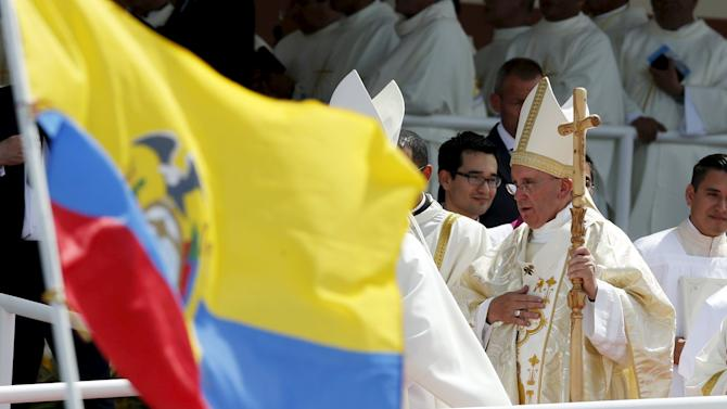 Pope Francis walks near the Ecuadorean flag after celebrating mass at Parque Samanes in Guayaquil