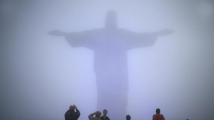 FILE - In this June 11, 2014 file photo, tourists stand below the Christ the Redeemer statue while it's covered by heavy fog, in Rio de Janeiro, Brazil. Rio's Archbishop Orani Tempesta presided over a ceremony Friday, July 11, 2014, marking the end to repairs made to the city's famed statue. The $856,000 repair project began six months ago after two fingers and part of the statue's head were chipped during lightning storms. (AP Photo/Hassan Ammar, File)