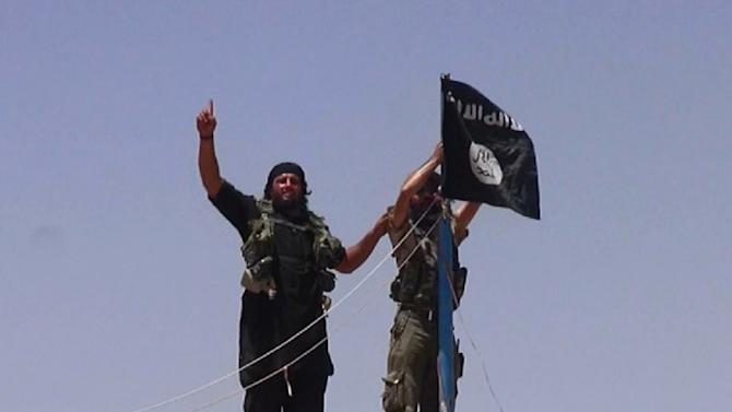 An image made available by the jihadist Twitter account Al-Baraka news on June 11, 2014 allegedly shows militants of the jihadist group Islamic State hanging their flag on a pole at a site on the Syrian-Iraqi border