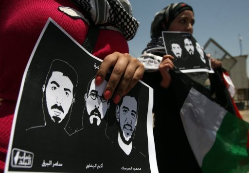 Palestinian protestors hold pictures of jailed footballer Mahmud Sarsak (right) and other prisoners during a demonstration near Ramallah on June 11. Sarsak, who has been refusing food for three months over being held in an Israeli jail without charge, on Monday agreed a deal with Israel for his early release, his lawyer said