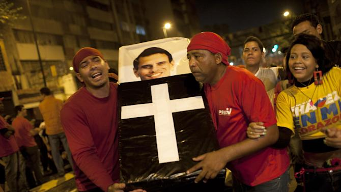 Supporters of Venezuela's President Hugo Chavez perform a mock funeral for opposition candidate Henrique Capriles as they celebrate in downtown Caracas, Venezuela, Sunday, Oct. 7, 2012.  Chavez won re-election and a new endorsement of his socialist project Sunday, surviving his closest race yet after a bitter campaign against Capriles.(AP Photo/Ariana Cubillos)