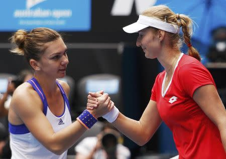 Makarova of Russia shakes hands with Halep of Romania after winning their women's singles quarter-final match at the Australian Open 2015 tennis tournament in Melbourne