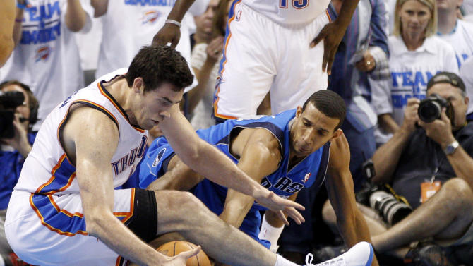 Oklahoma City Thunder center Nick Collison, left, and Dallas Mavericks forward Brandan Wright, right, reach for a loose ball in the first quarter of Game 2 in the first round of the NBA basketball playoffs, in Oklahoma City, Monday, April 30, 2012. (AP Photo/Sue Ogrocki)