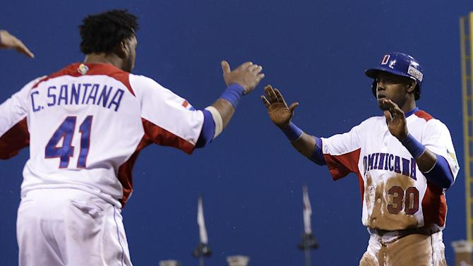 The Dominican Republic's Alejandro De Aza (30) is congratulated by Carlos Santana after scoring against Puerto Rico during the fifth inning of the championship game of the World Baseball Classic in San Francisco, Tuesday, March 19, 2013. (AP Photo/Ben Margot)
