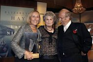"Author Elizabeth Hay (L) holds the Giller Prize, Canada's richest literary award, for her novel ""Late Nights On Air"" as she is congratulated by fellow Canadian writer Alice Munroe (C) and award founder Jack Rabinovitch at the end of the Giller awards ceremony in Toronto November 6, 2007. REUTERS/ Mike Cassese/Files"
