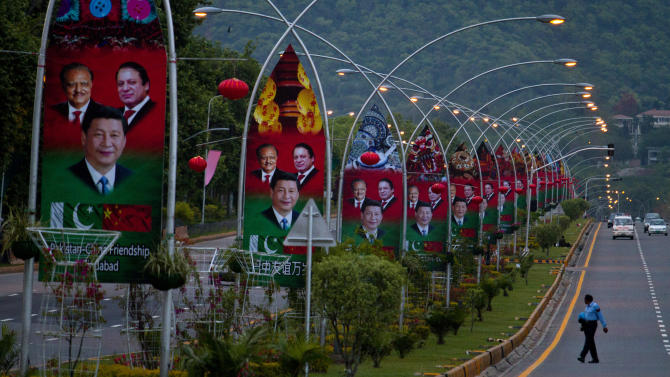 A Pakistani police officer walks pasts billboards showing pictures of Chinese President Xi Jinping, center, with Pakistan's President Mamnoon Hussain, left, and Prime Minister Nawaz Sharif welcoming Xi Jingping to Islamabad, Pakistan, Sunday, April 19, 2015. Chinese President Xi Jinping will arrive in Pakistan on April 20 to oversee agreements on pipelines, power plants and other projects as part of a massive $46 billion joint development program that Beijing hopes will stabilize its longtime ally's economy and extend China's influence in western Asia. (AP Photo/Anjum Naveed)
